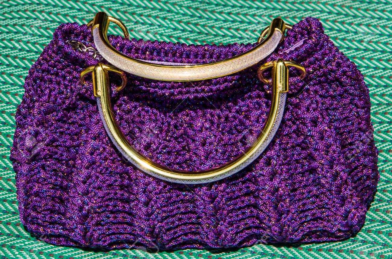 Purple crocheting hand bag on green mat.
