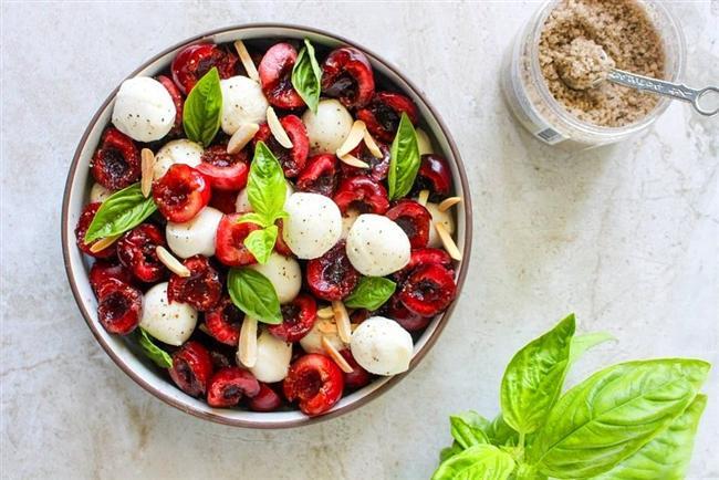 Genellikle fesleğen, domates ve mozarellayla yapılan caprese salatasına biraz yaz getirip tatlılık katalım dedim. Emin olun bütün ön yargılarınızı kırıp salataya meyve katma nedeniniz bu salata olacak. Üstelik yapılışı çok kolay.    Minik top mozarellaları bir kaba alın daha sonra baharatlar ve zeytinyağı ile tatlandırın. Daha sonra kirazların çekirdeklerini çıkarın fesleğenlerle birlikte hepsini karıştırın.